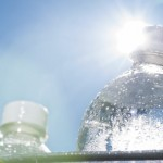 A close-up of a plastic water bottle in a bucket of ice as the Sun shines down on a hot Summer day. It is a good idea to keep hydrated while doing activities on a hot day.