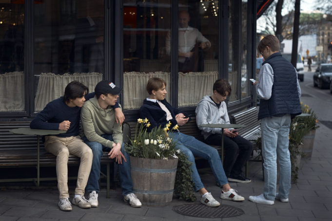 FILE - In this Wednesday, April 8, 2020 file photo youths hang out outside a restaurant in Stockholm, Sweden. (AP Photo/Andres Kudacki, File)