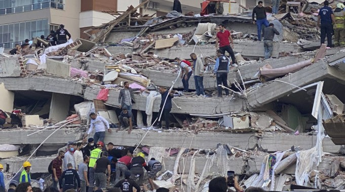 Rescue workers and local people try to save residents trapped in the debris of a collapsed building, in Izmir, Turkey, Friday, Oct. 30, 2020. A strong earthquake struck Friday in the Aegean Sea between the Turkish coast and the Greek island of Samos, collapsing buildings in the city of Izmir in western Turkey, and officials said at least six people were killed and scores were injured.(AP Photo/Ismail Gokmen)