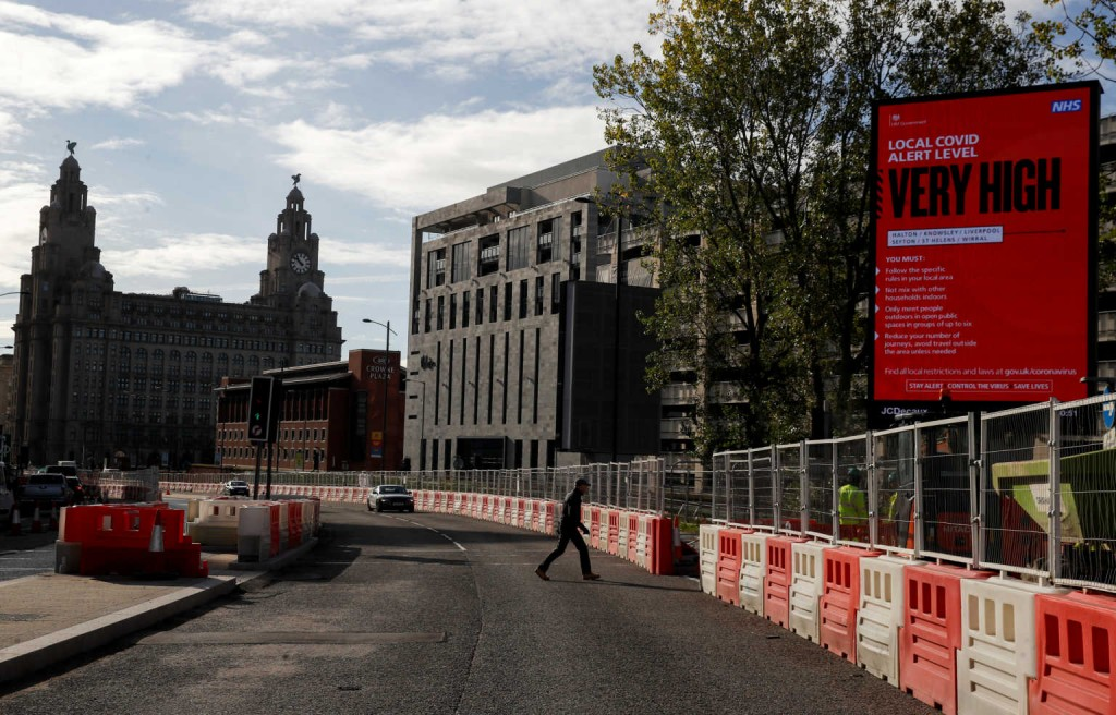A covid warning sign stands in the vicinity of the Royal Liver building, as the spread of the coronavirus disease (COVID-19) continues, in Liverpool, Britain October 15, 2020. REUTERS/Phil Noble