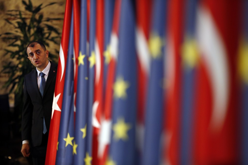 An official helps to adjust Turkey's and European flags prior to the opening session of a high-level meeting between EU and Turkey, in Istanbul, Thursday, Feb. 28, 2019.  The high-level talks are aimed at improving economic and business ties between Turkey and European Union. (AP Photo/Lefteris Pitarakis)