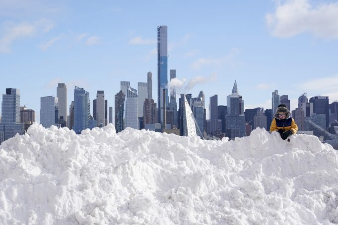 A boy plays on a mound of snow in front of the skyline of New York City in West New York, N.J., Thursday, Dec. 17, 2020. The first major snowstorm of the season left the Northeast blanketed in snow, setting records in some areas. (AP Photo/Seth Wenig)