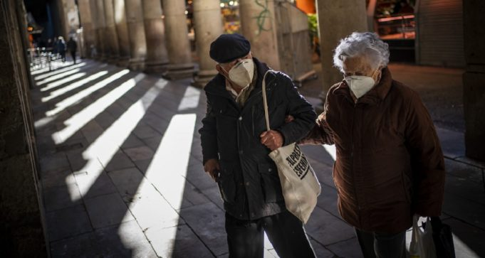 A couple wearing face masks against the spread of Coronavirus walk in a market in Barcelona, Spain, Friday, Jan. 22, 2021. Although health authorities believe that the surge of coronavirus infections is waning, the rate of contagion has shot to over three times the extreme risk level, dangerously straining the health system. (AP Photo/Emilio Morenatti)